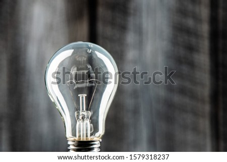 Classic light bulb on front of rustical wall.