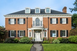 Classic luxurious red brick house with green lawn
