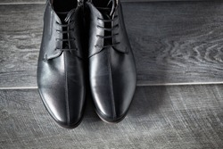 Classic male black leather shoes on wooden background