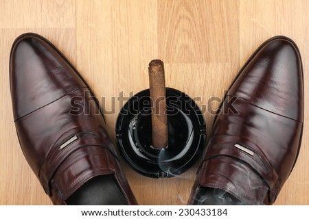 Classic men\'s shoes, ashtray and  fuming cigar on the wooden floor