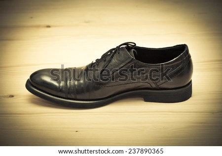 Classic men\'s shoes. Retro style, photo toned in yellow.  Black shoes