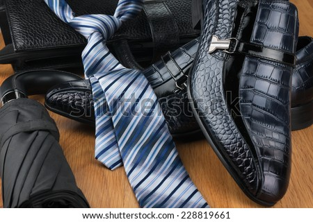 Classic men\'s shoes, tie, umbrella and bag on the wooden floor, can be used as background