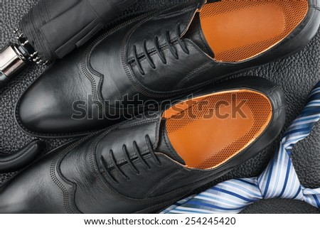 Classic men\'s shoes, tie, umbrella on the black leather, can be used as background