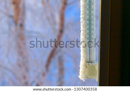 Classic mercury thermometer for measuring ambient temperature, hanging outside the window, with readings minus 70 degrees Celsius. Minus 70 degrees below zero.