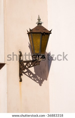 Classic metal lantern on yellow stone wall. Clipping path for object included.