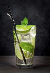 Classic Mojito cocktail with rum, lime and mint on wooden table in front of dark wall