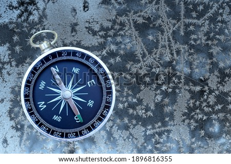 Classic navigation compass on winter frozen background as symbol of tourism with compass, travel with compass and outdoor activities with compass
