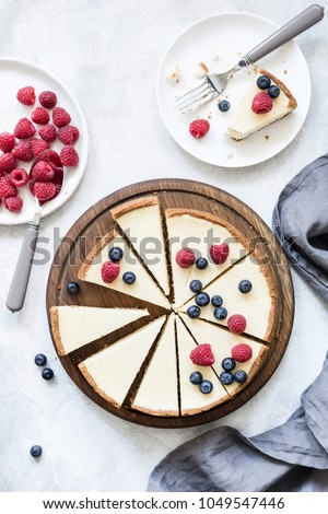 Classic New York cheesecake with fresh raspberries and blueberries on white concrete background, top view #1049547446