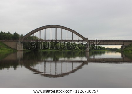 Classic old arched railway bridge over the river - view from the water on a summer day against the trees on the shore and gray cloudy sky #1126708967