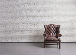 classic old brown leather sofa, white brick wall textured wooden laminate flooring, empty space