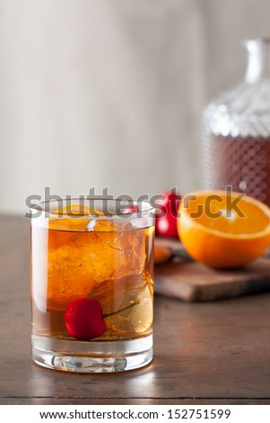 Classic old-fashioned cocktail with a cherry on a wooden table