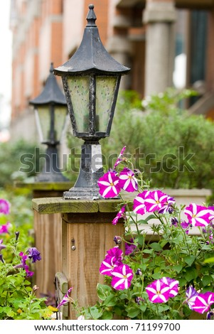 Classic old garden lamp with blooming colorful Petunia flowers - stock photo