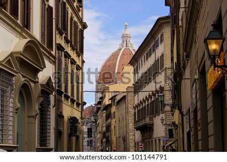 Classic old street in the center of Florence, Italy with duomo dome in background - stock photo
