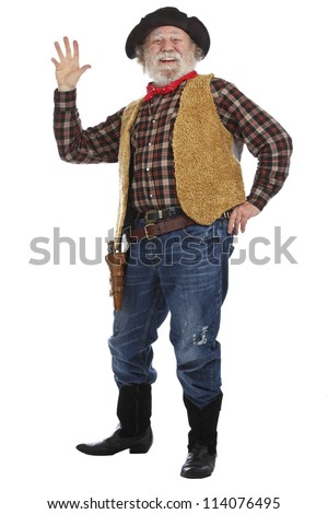 Classic old west smiling cowboy with felt hat, grey whiskers, revolver, stands and waves. Isolated on white background, copy space, vertical.