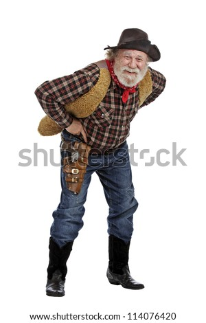 Classic old west smiling cowboy with felt hat, grey whiskers, revolver, stands bending forward. Isolated on white background, copy space, vertical.
