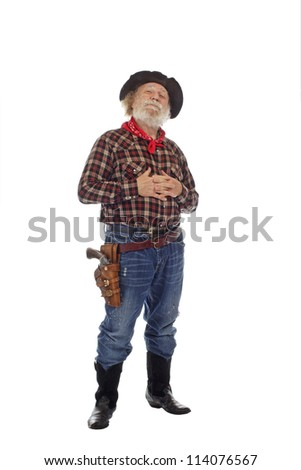 Classic Old West style cowboy with felt hat, grey whiskers, revolver, stands clasping hands against chest. Isolated on white background, copy space, vertical.