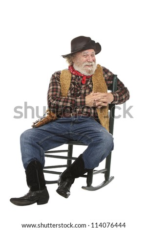 Classic old west style smiling cowboy with felt hat, grey whiskers, revolver. He sits in a rocking chair. Isolated on white, vertical, copy space.