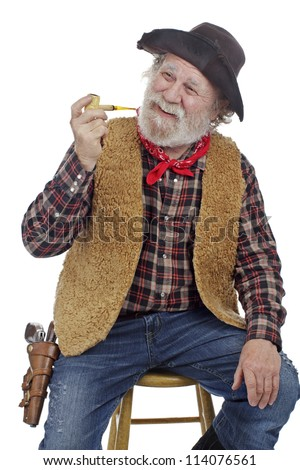 Classic Old West style smiling cowboy with felt hat, grey whiskers, revolver, holds corn cob pipe and sits on stool. Isolated on white, vertical, copy space.