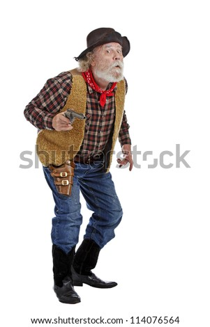 Classic old west worried cowboy with felt hat, grey whiskers, revolver, stands ready with revolver. Isolated on white background, copy space, vertical.