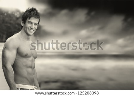 Classic outdoor portrait of a great looking shirtless muscular male model against dramatic skyscape in monochrome