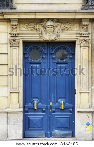 Classic painted wooden door with bronze handles in Paris