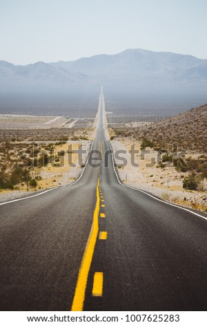 Classic panorama view of an endless straight road running through the barren scenery of the American Southwest with extreme heat haze on a beautiful sunny day with blue sky in summer