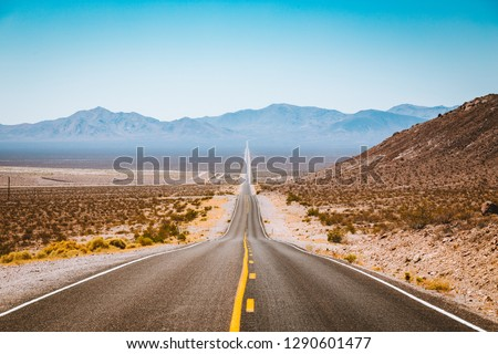 Classic panorama view of an endless straight road running through the barren scenery of the American Southwest with extreme heat haze on a beautiful sunny day with blue sky in summer #1290601477