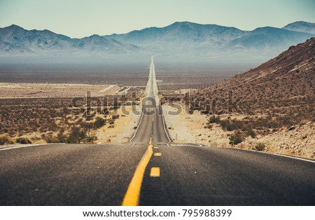 Classic panorama view of an endless straight road running through the barren scenery of the American Southwest with extreme heat haze on a beautiful sunny day with blue sky in summer #795988399