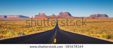 Shutterstock Classic panorama view of historic U.S. Route 163 running through famous Monument Valley in beautiful golden evening light at sunset on a beautiful sunny day with blue sky in summer, Utah, USA