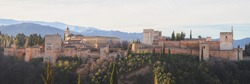 Classic panoramic sunrise view Charles V Palace, the iconic Alhambra and Sierra Nevada Mountains from Mirador de San Nicolas in the albaicin old town of Granada, Andalusia, Spain.