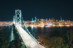 Classic panoramic view of scenic San Francisco skyline with famous Oakland Bay Bridge and traffic light trails illuminated in beautiful evening twilight at dusk in summer, SF Bay Area, California, USA