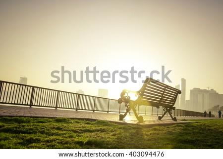 Classic park bench from below angle against morning sun. A beautiful winter morning at the park.
