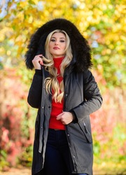 Classic parka coat has become wardrobe icon. Versatile functional and stylish. Girl wear parka while walk park. Puffer jacket with hood. Woman wear black parka fur hood. Youth hipster fashion concept.