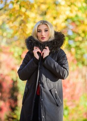 Classic parka coat has become wardrobe icon. Versatile functional and stylish. Girl wear parka while walk park. Autumn season fashion concept. Puffer jacket with hood. Woman wear black parka fur hood.