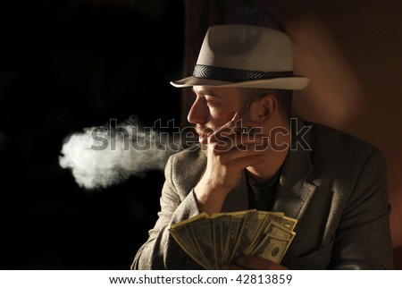 classic portrait of young gangster smoking and count dollars