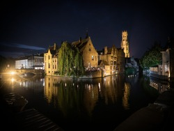 Classic postcard view illuminated historical medieval buildings Rozenhoedkaai Dijver canal belfry belfort Bruges Belgium