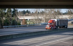 Classic powerful big rig orange semi truck tractor with sleeping compartment cab transporting commercial  cargo in dry van semi trailer moving on divided highway road with overpass intersection