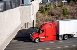 Classic powerful big rig red semi truck tractor with day cab and roof spoiler transporting commercial  cargo in dry van semi trailer moving on the highway fork intersection with bridge across