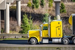 Classic powerful big rig yellow semi truck tractor with sleeping compartment and roof spoiler transporting commercial  cargo in dry van semi trailer moving on the highway road with bridge across