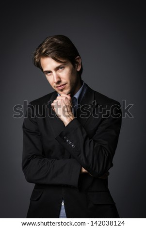 Classic profile portrait of a young business man wearing suit, isolated on gray background.