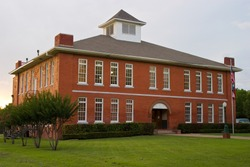Classic red brick schoolhouse in typical small town USA location.