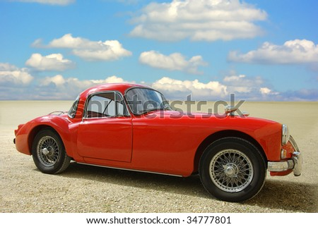 Classic red cabriolet on a background of the blue sky.