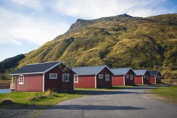 Classic red scandinavian fishing cabins huts near water in summer landscape, Norway, Iceland