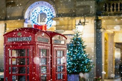 Classic, red telephone booths with snow falling in front of Christmas decorations lights in the Covent Garden area, London, United Kingdom