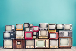 Classic retro CRT TV receivers set collection from circa 50s, 60s, 70s and 80s of XX century front mint blue wall background. Media broadcasting or live news concept. Vintage old style filtered photo