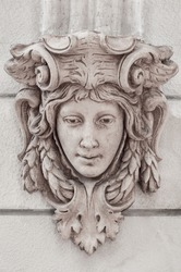 Classic roman head sculpture mounted on wall.