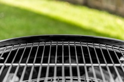 Classic round black BBQ with a clean metal grill shot close up at an angle outside on a sunny day.