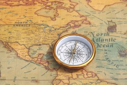 Classic round compass on background of old vintage map of world as symbol of tourism with compass, travel with compass and outdoor activities with compass