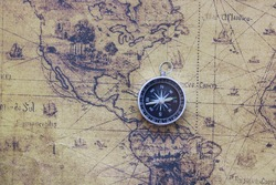 Classic round compass on background of old vintage map of world as symbol of tourism with map, travel with map and outdoor activities with map