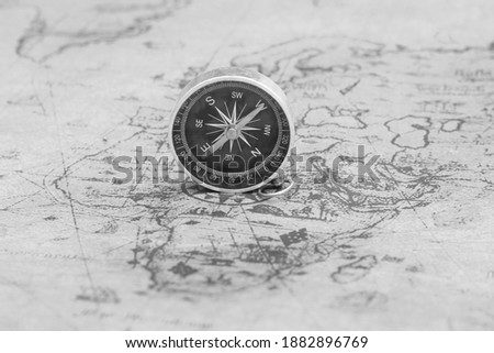 Classic round compass on old vintage map depicting North America and the United States of America as symbol of tourism with compass, travel with compass and outdoor activities with compass